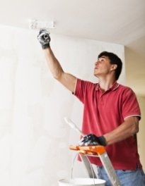 Man painting ceiling using paint for mold